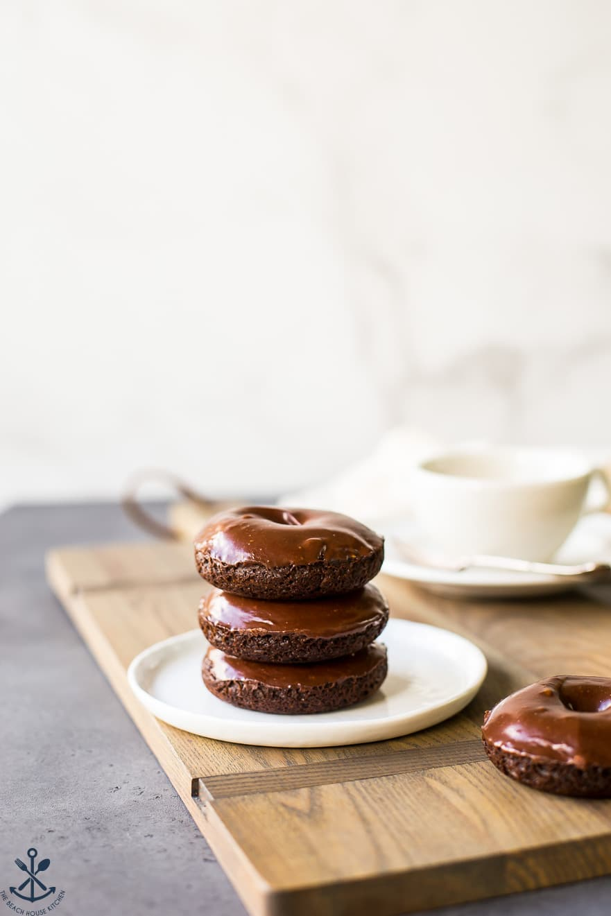 Stack of three cocoa coffee baked donuts on a white plate