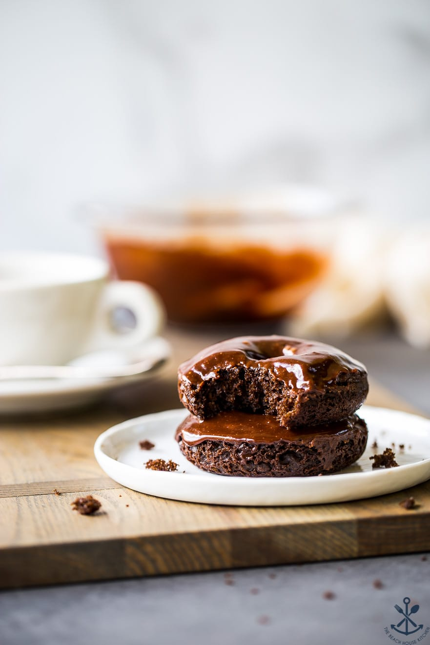 Two cocoa coffee baked donuts stacked on a white plate