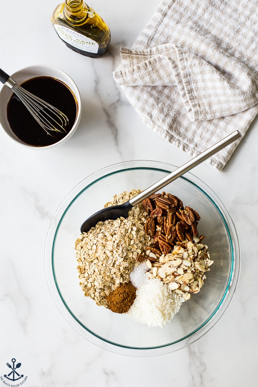 Overhead photo of glass bowl filled with ingredients for maple cinnamon granola