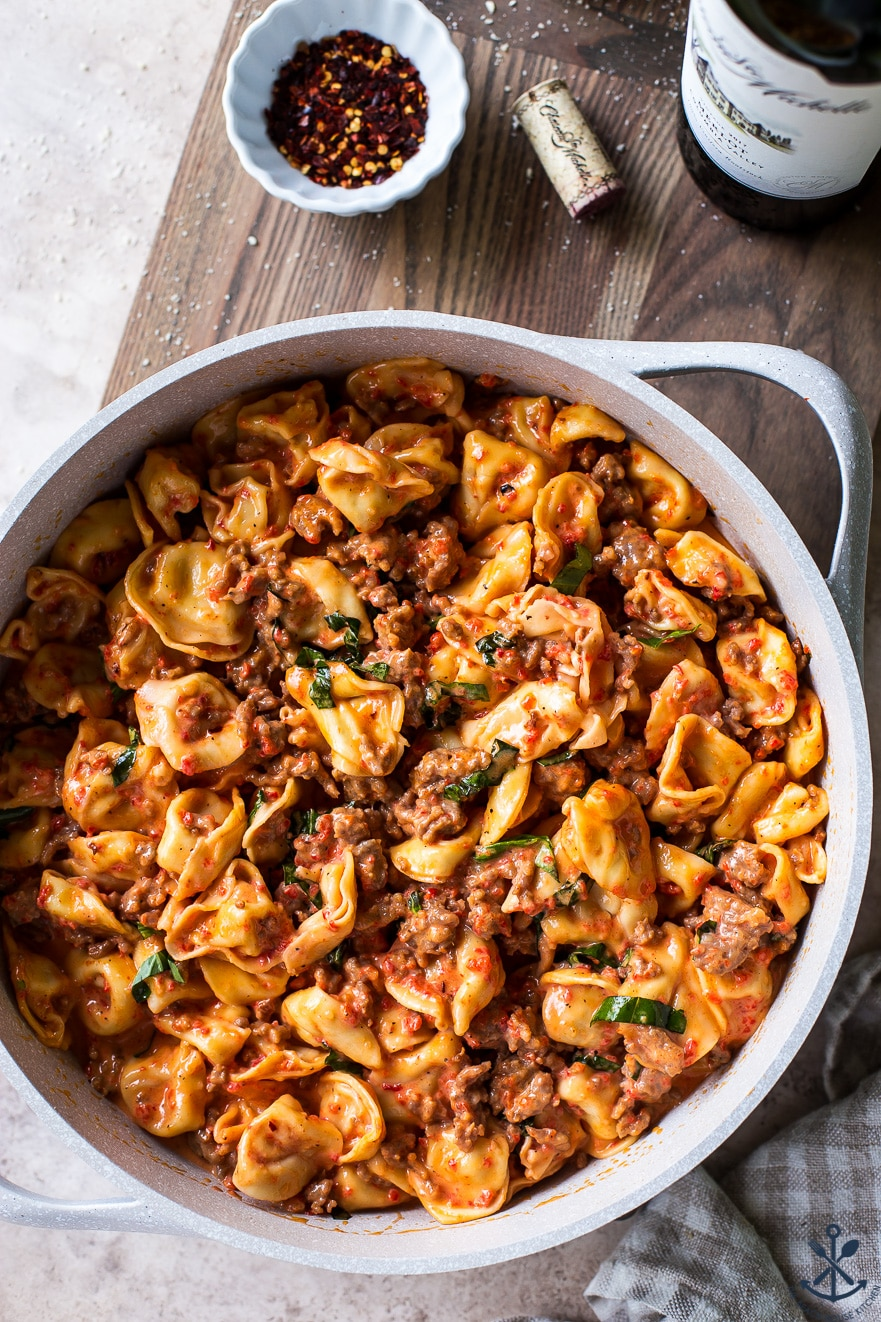 Overhead photo of Roasted Red Pepper Tortellini Alfredo with Sausage in a pan