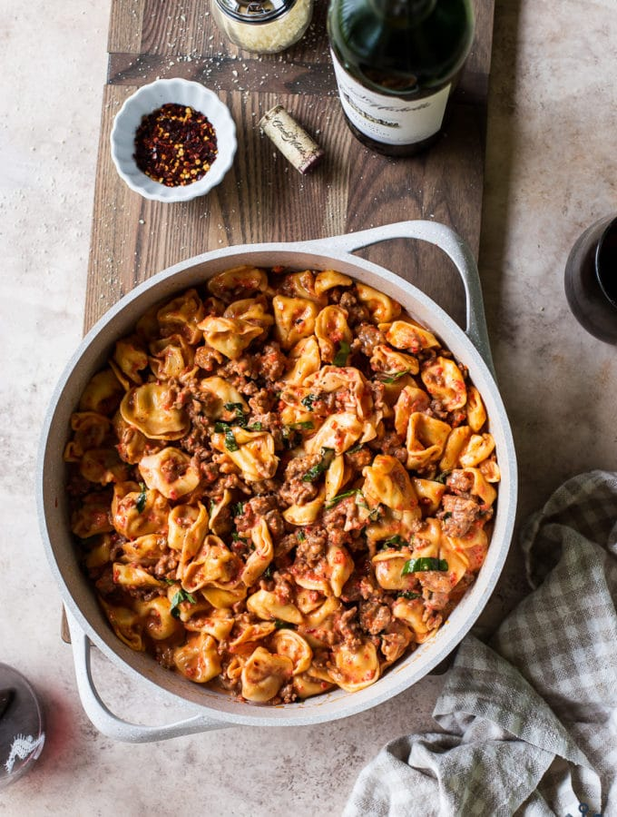 Overhead photo of pan filled with roasted red pepper tortellini alfredo with Italian Sausage