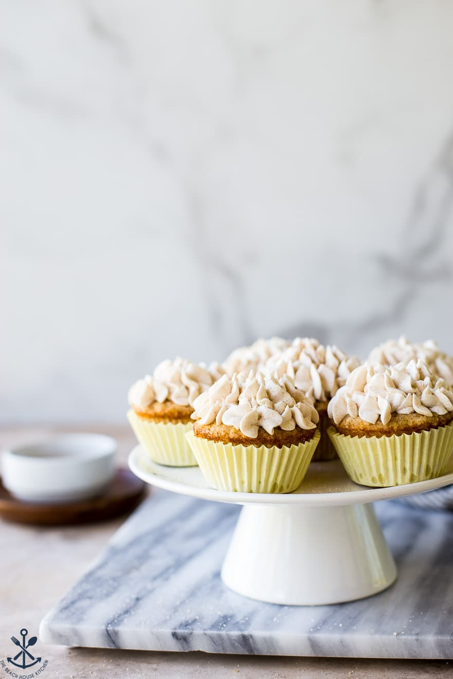 Snickerdoodle Cupcakes with Cinnamon Buttercream on a white cake stand on a marble board