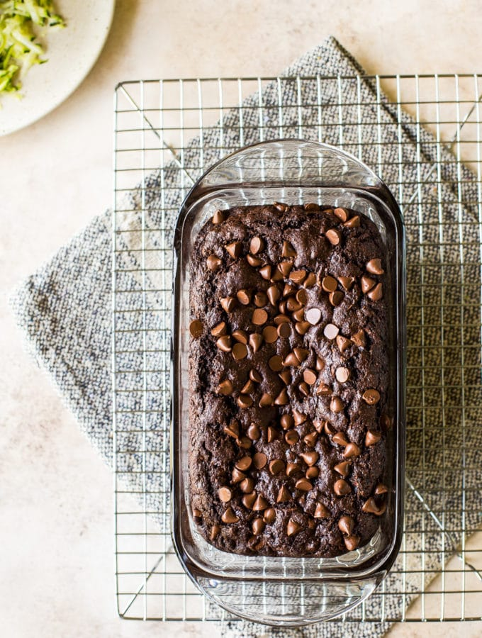 Overhead photo of chocolate zucchini bread in glass loaf pan on wire rack