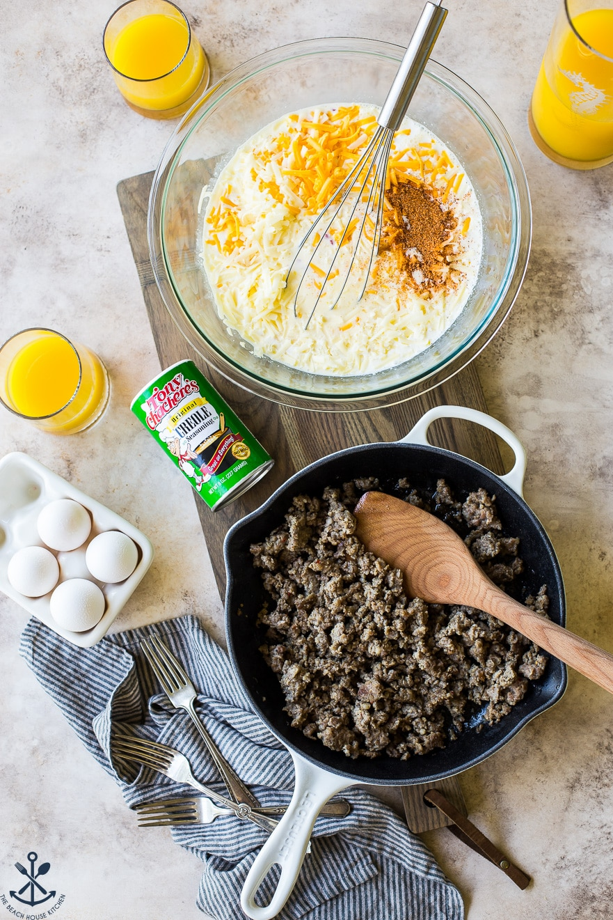 Overhead photo of ingredients for Creole Breakfast Egg Bake with Sausage and Potatoes on a wooden board