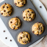 Overhead photo of Easy Chocolate Chip Muffins in muffin tin on a round white marble board
