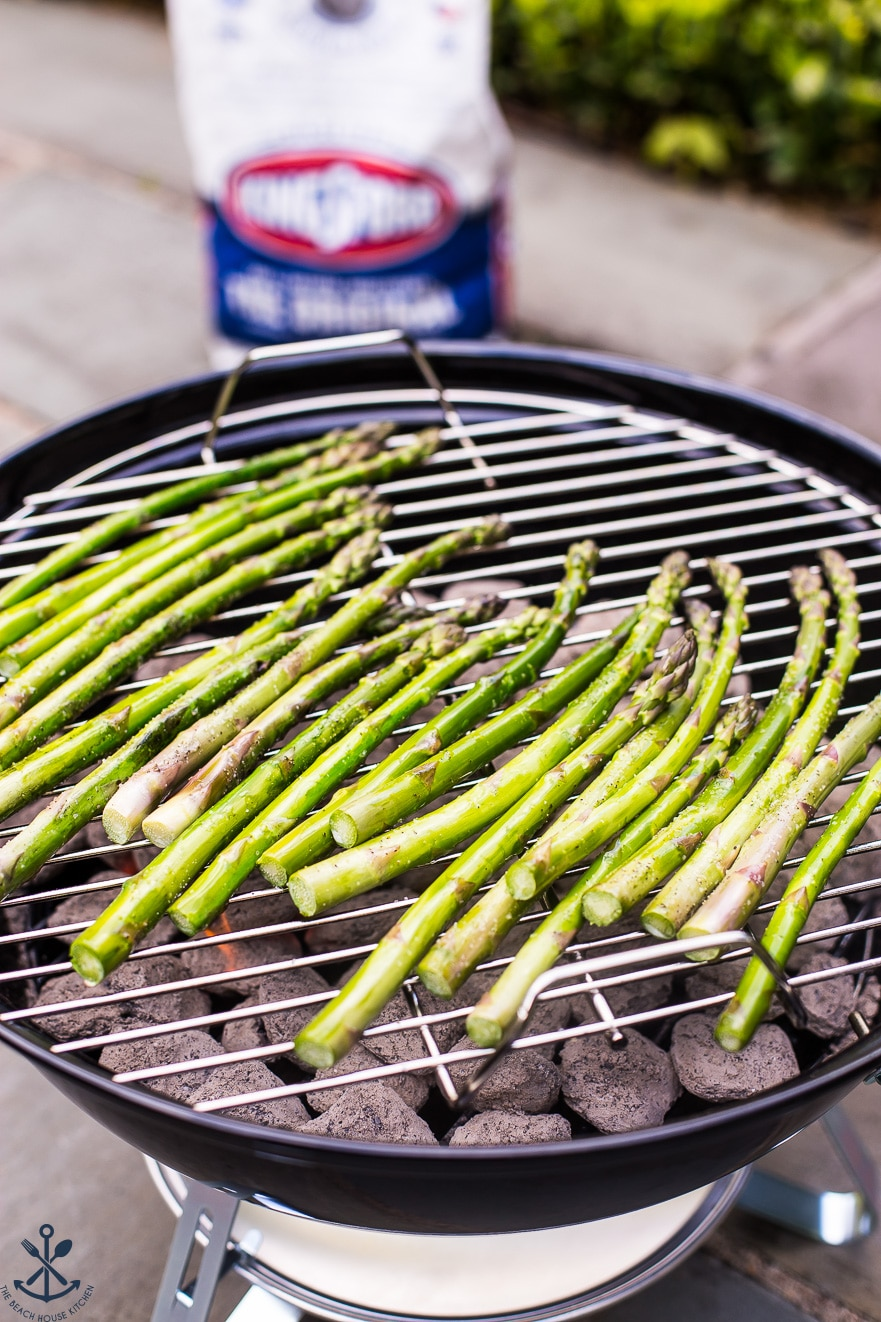 Asparagus grilling on a small round charcoal grill