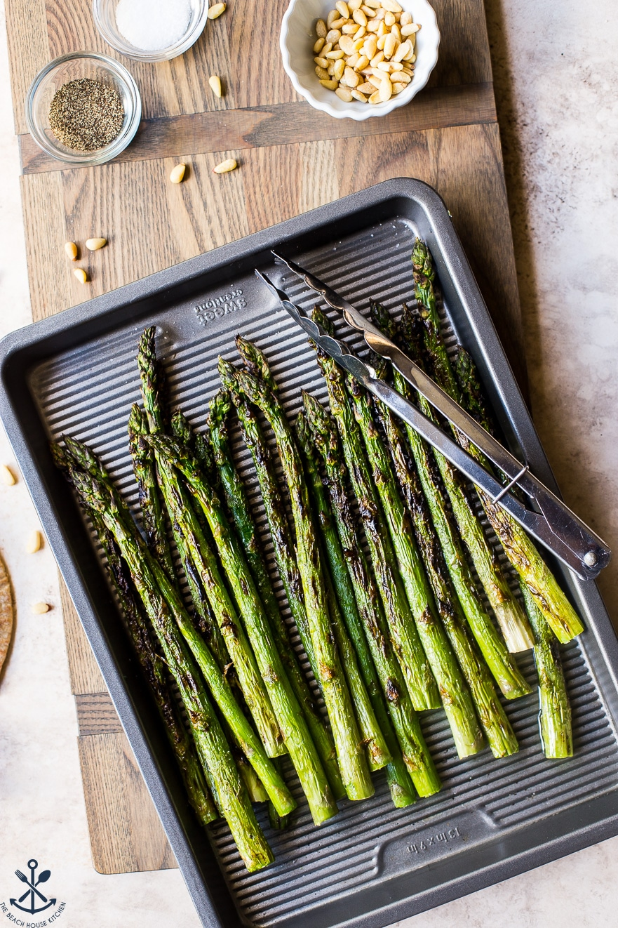 Overhead photo of grilled asparagus on a silver baking sheet with a pair of tongs