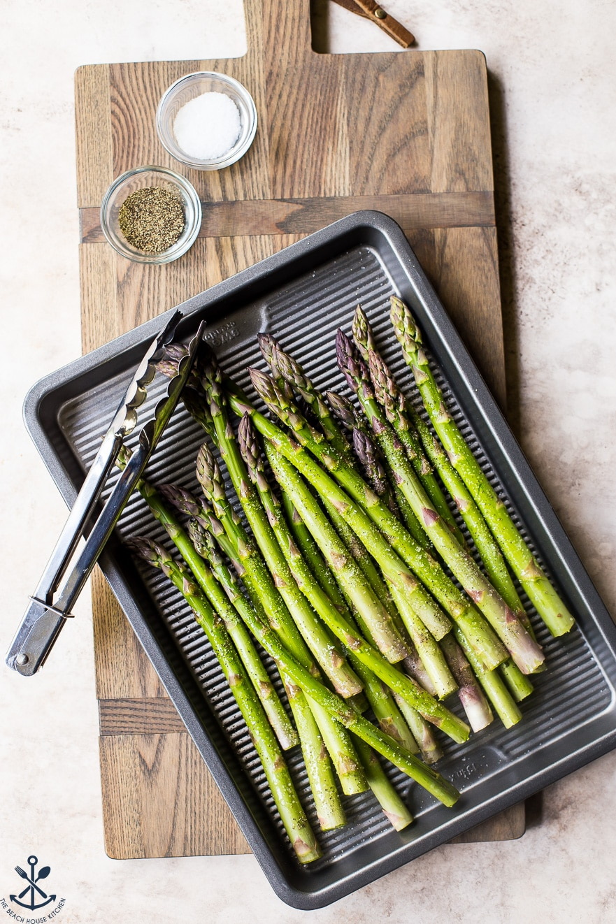 Pre-grilled asparagus on a silver baking sheet with a set of tongs
