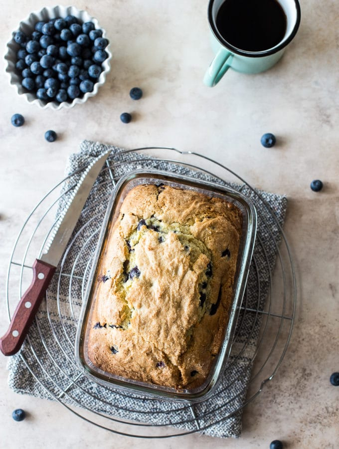Overhead photo of blueberry lemon loaf on a round wire rack with a bowl of blueberries and a cup of coffee