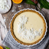 Overhead photo of an orange cream tart on a round wire rack surrounded by halved oranges