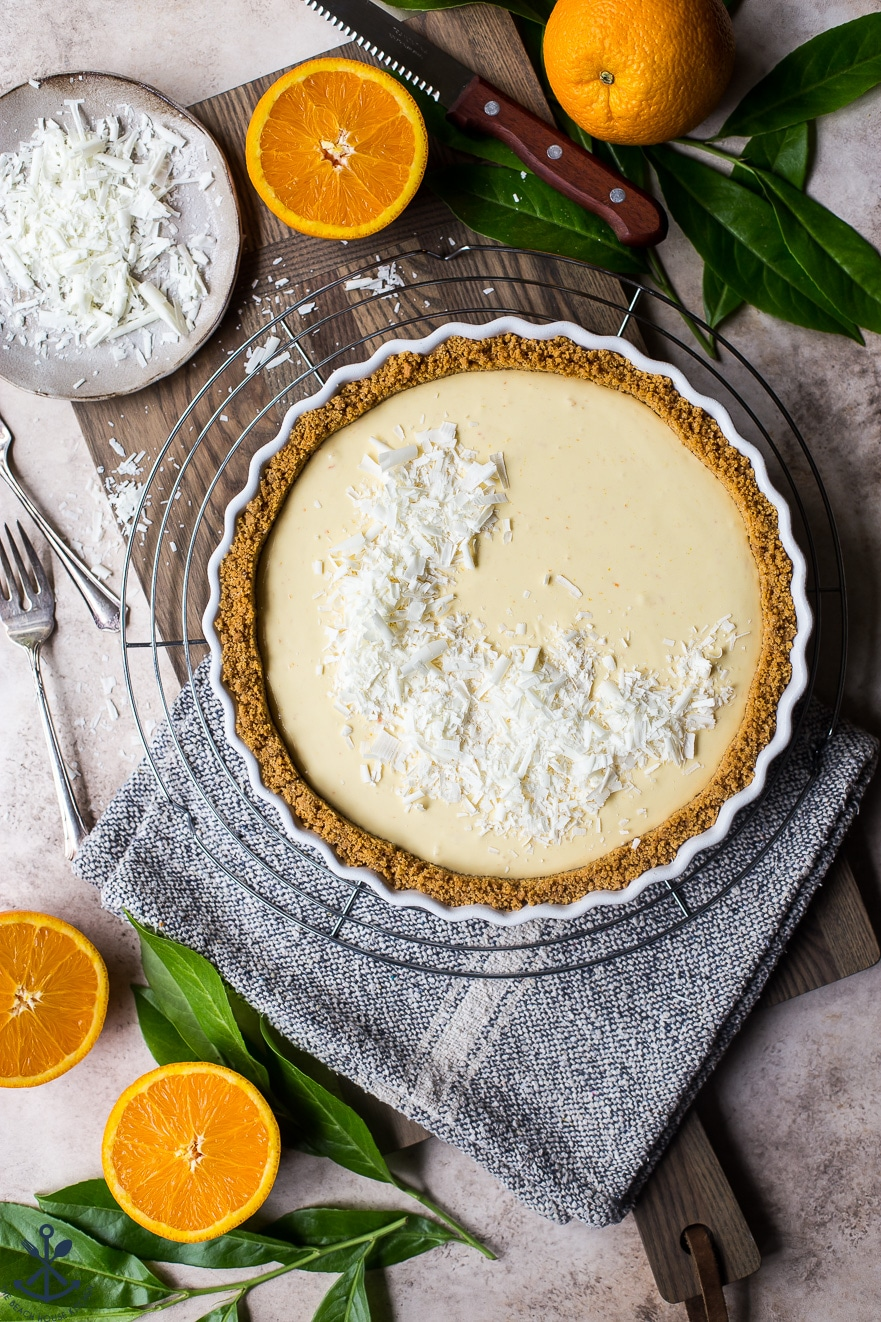 Overhead photo of orange cream tart on round wire rack surrounded by oranges