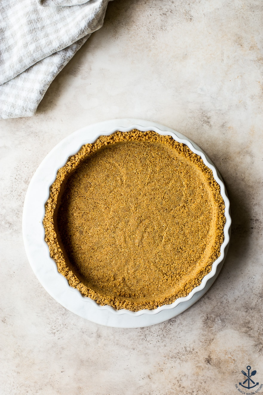 Overhead photo of graham cracker crust on a white round marble board