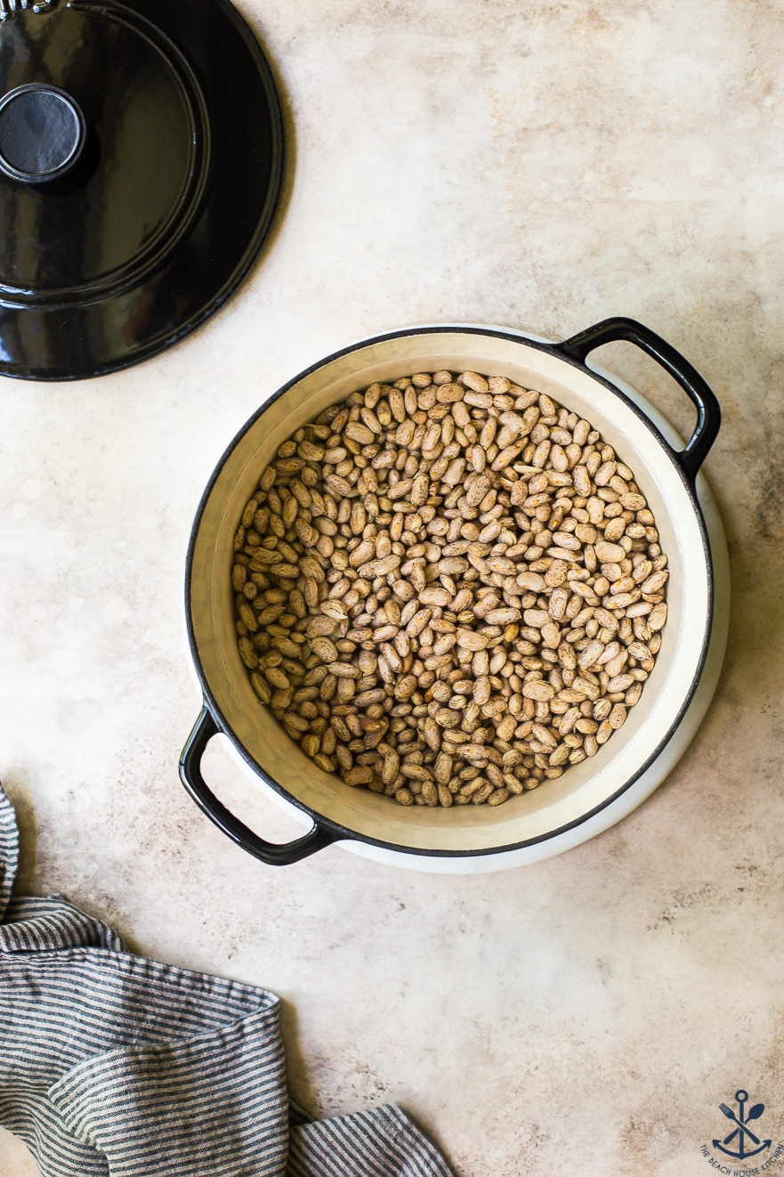 Overhead photo of large pot filled with dried pinto beans and water