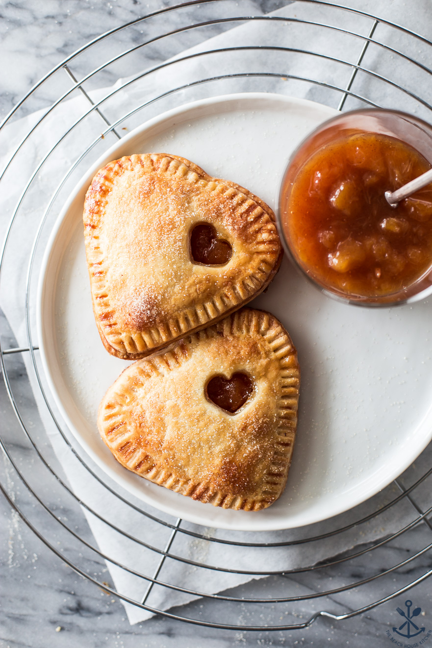Overehead photo of two heart shaped peach hand pies on a white plate on a wire rack