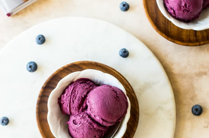 Overhead photo of white dishle board filled with dark purple blueberry ice cream on round marb