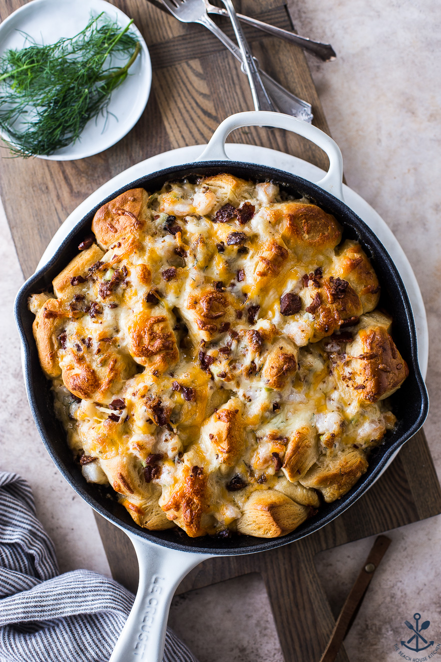 Overhead photo of cheesy shrimp skillet monkey bread in a white skiller on a wood board