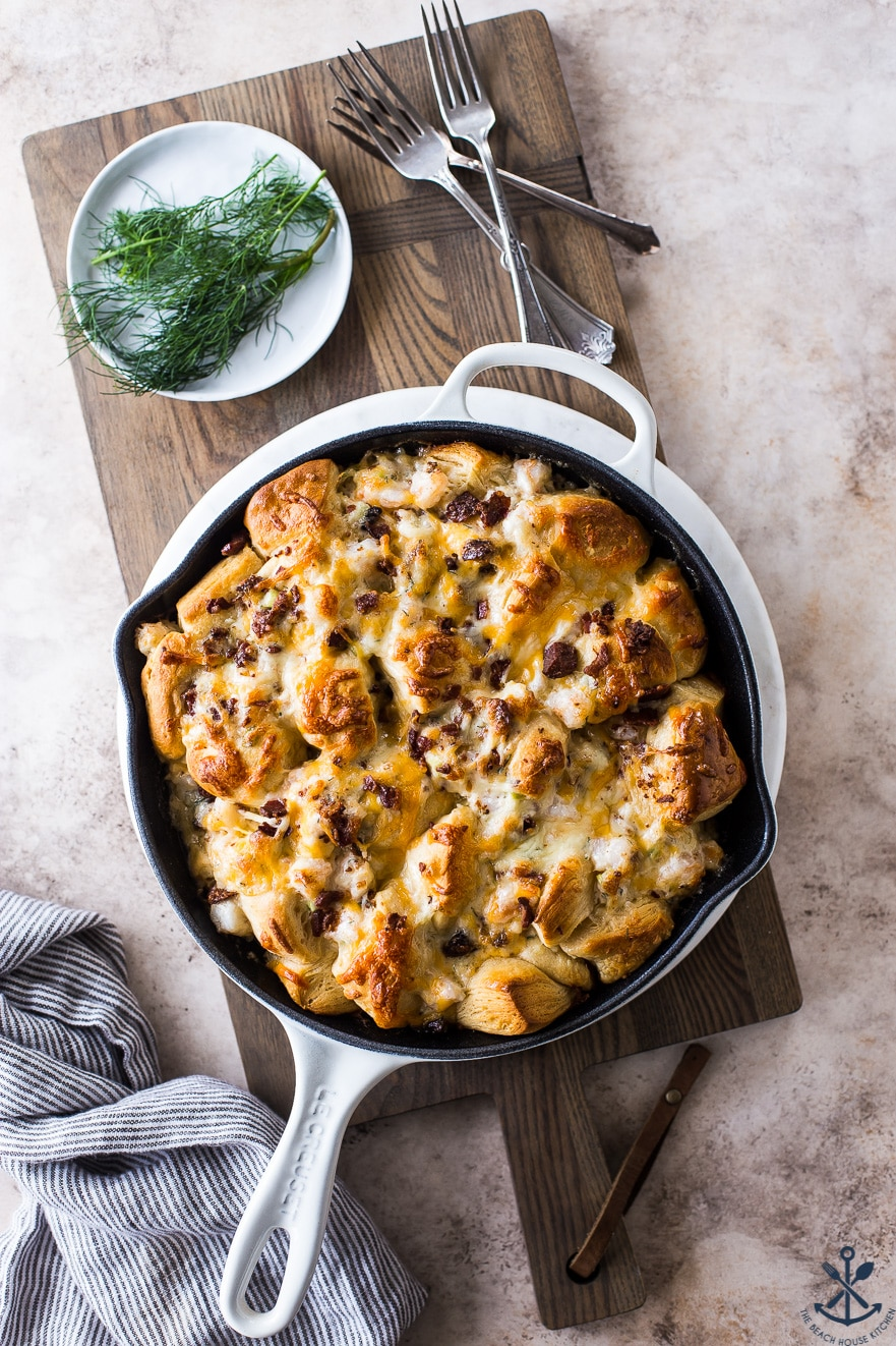 Cheesy Shrimp Skillet Monkey Bread in a white skillet on a wooden board