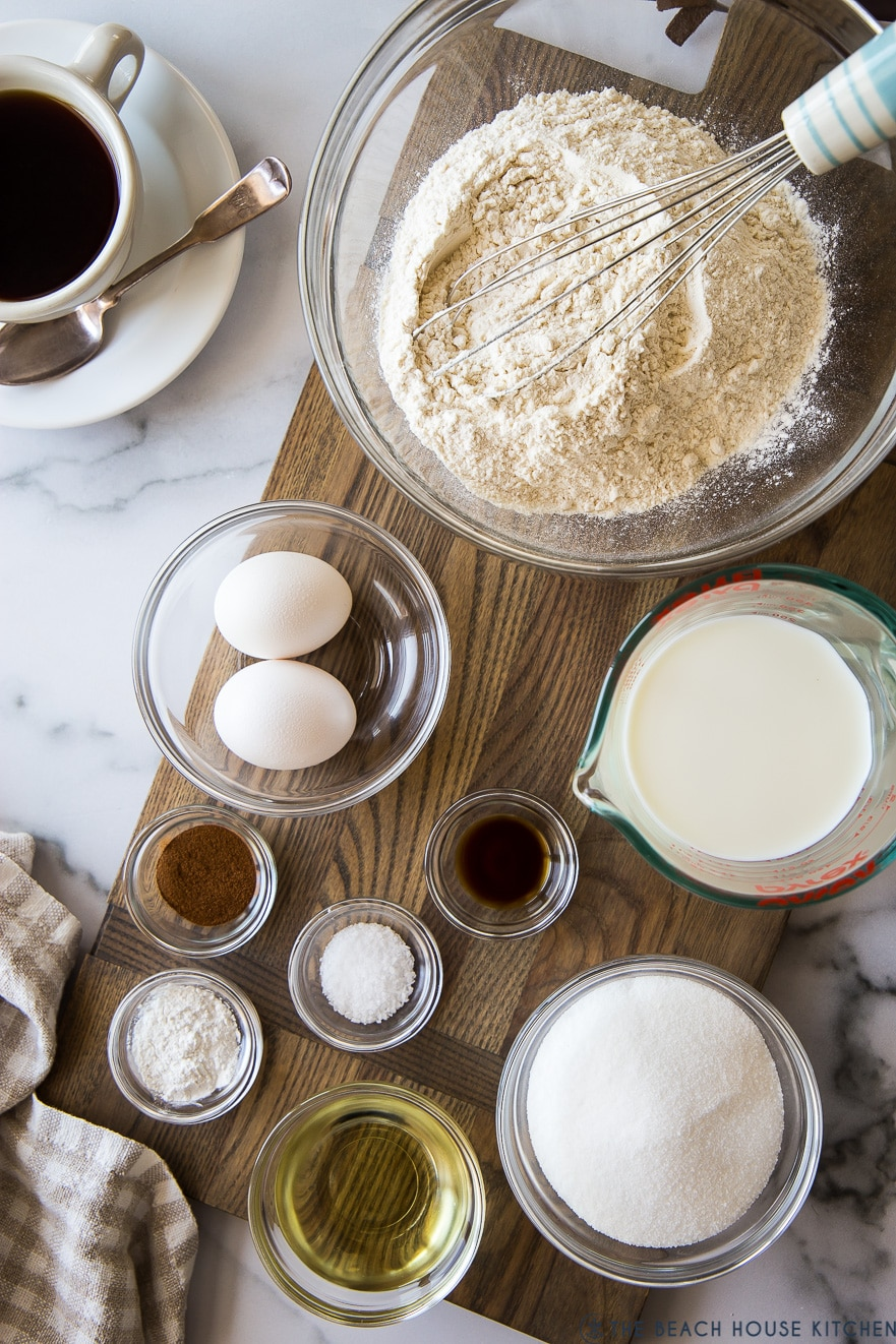 Overhead photo of ingredients for cinnamon streusel quick bread in glass bowls on a wooden board