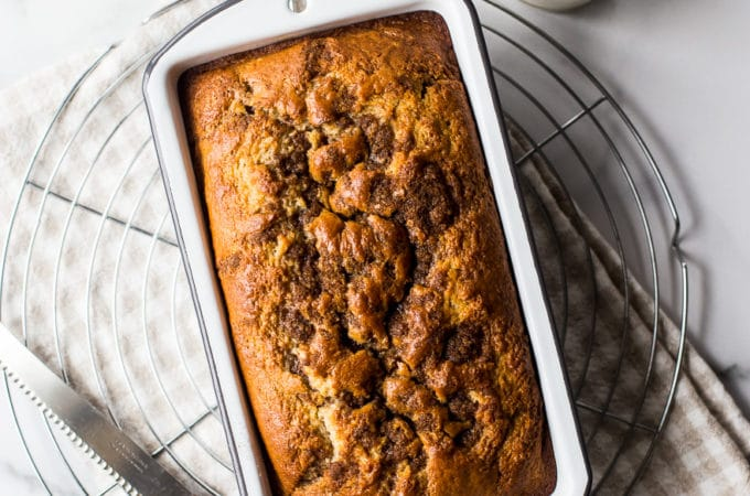 Overhead photo of a loaf of cinnamon streusel quick bread on a round wire rack