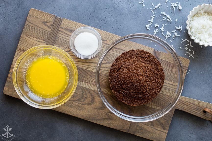Ingredients for chocolate graham cracker crust in three glass bowls on wooden board