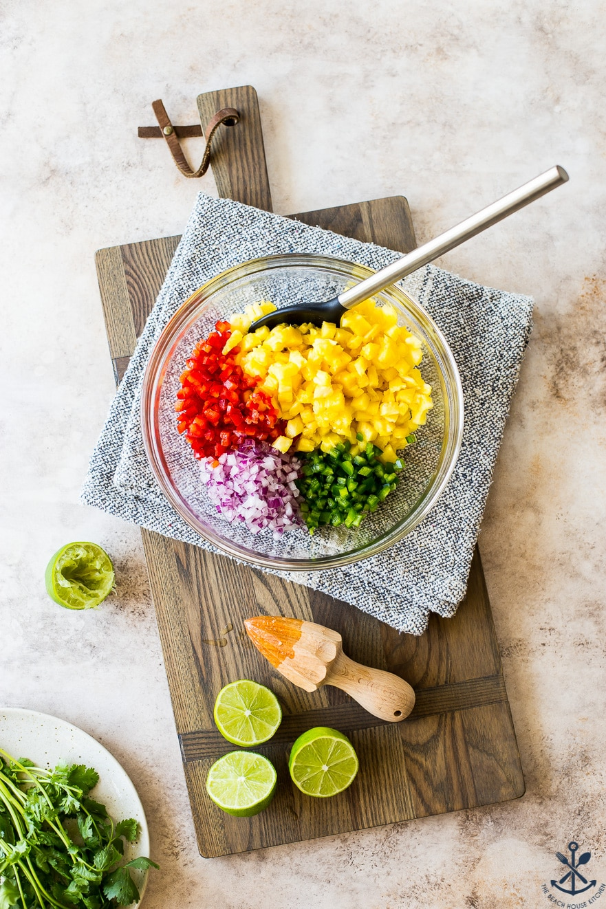 Overhead photo of glass bowl filled with ingredients for pineapple salsa