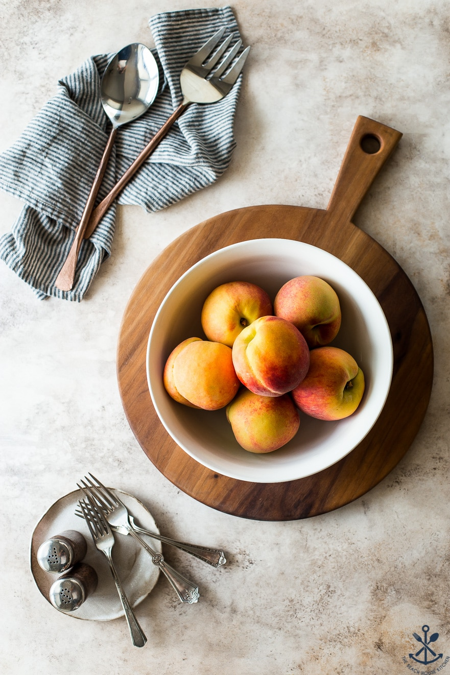 A white bowl filled with peaches on a round wood board