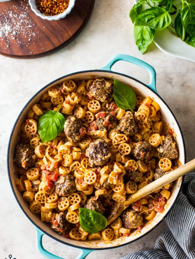 Creamy Tomato Pasta with Meatballs in a round turquoise colored baking dish