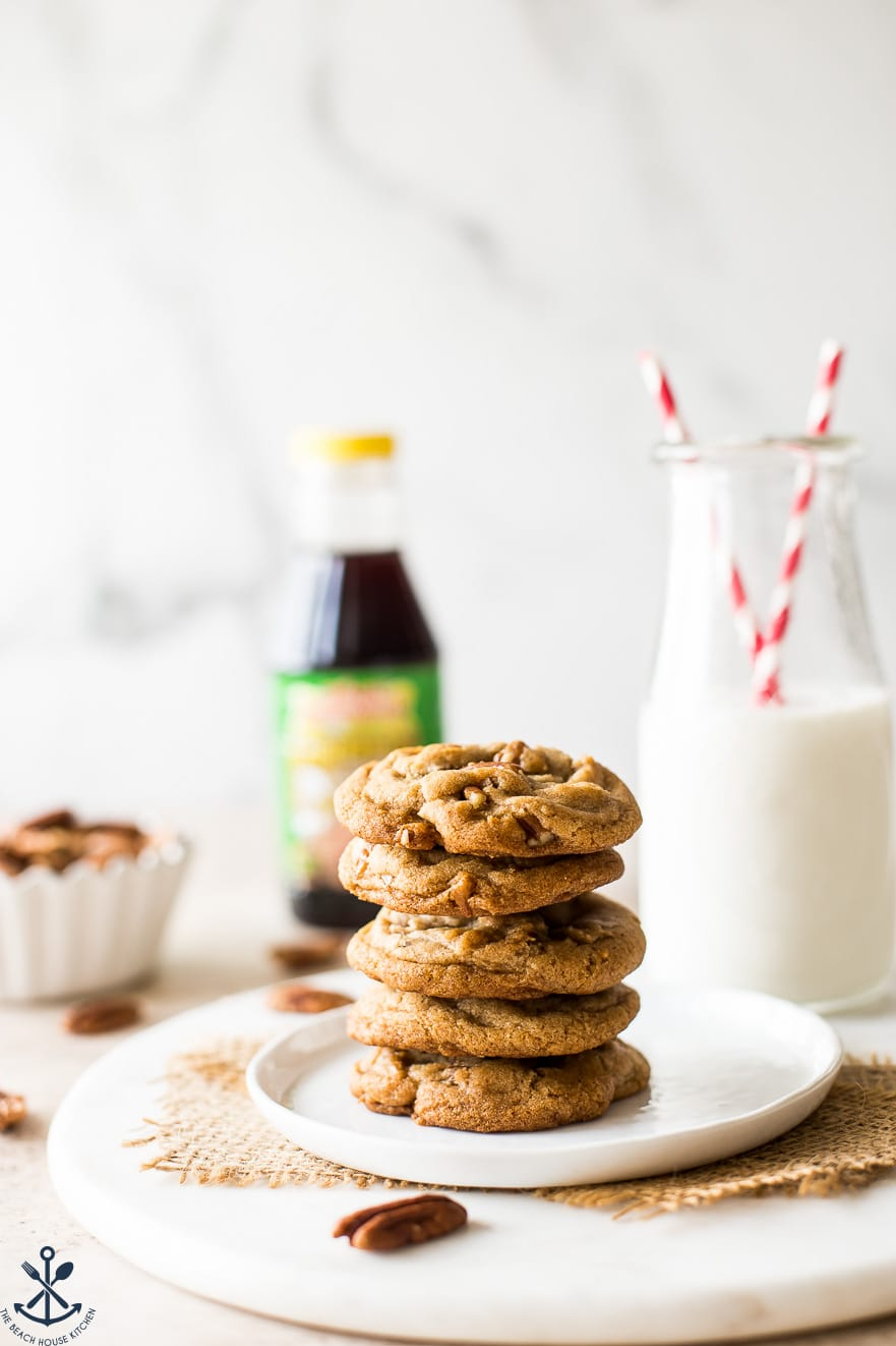 A stack of cookies on a white plate with a bottle of milk in the background