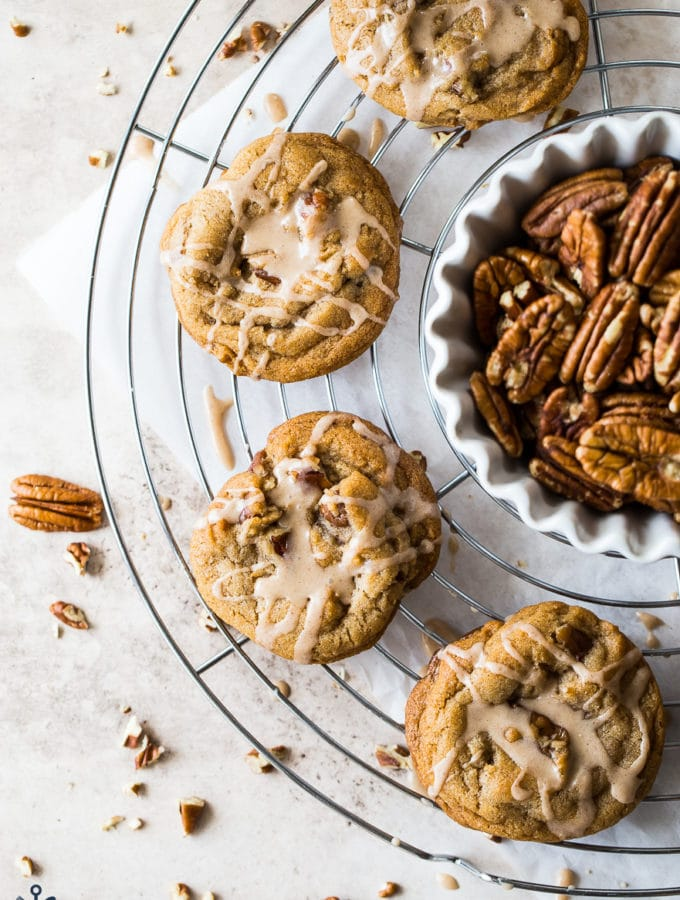 Overhead photo of Brown Sugar Praline Cookies with Praline Cinnamon Glaze on a wire rack with a bowl of pecans