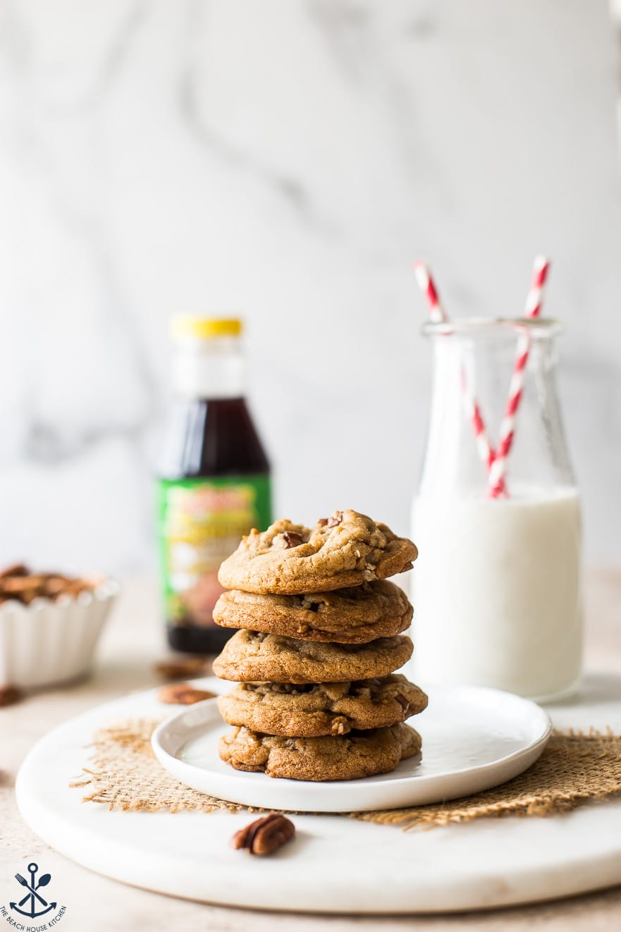 A stack of Brown Sugar Praline Cookies with Praline Cinnamon Glaze on a white plate with a bottle of milk