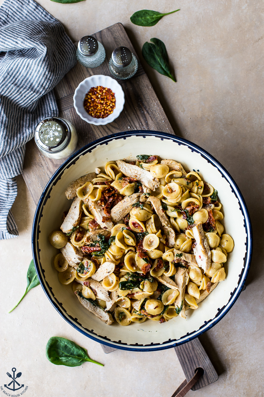 Chicken Pasta with Sun-Dried Tomato Bacon Cream Sauce in a large bowl on a wooden board
