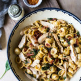 Chicken Pasta with Sun-Dried Tomato Bacon Cream Sauce in a bowl on a wooden board
