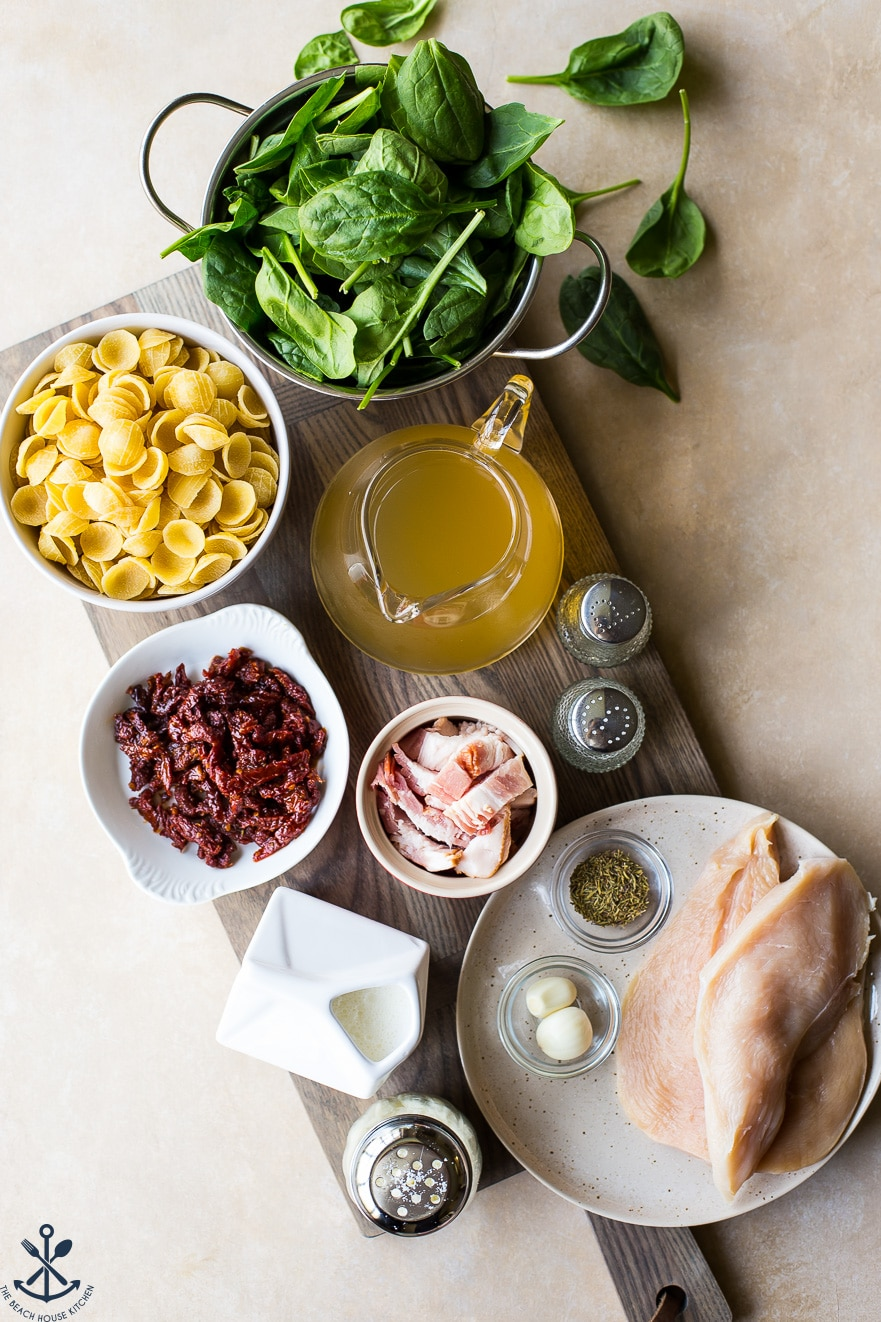 Ingredients for Chicken Pasta with Sun-Dried Tomato Bacon Cream Sauce on a wooden board