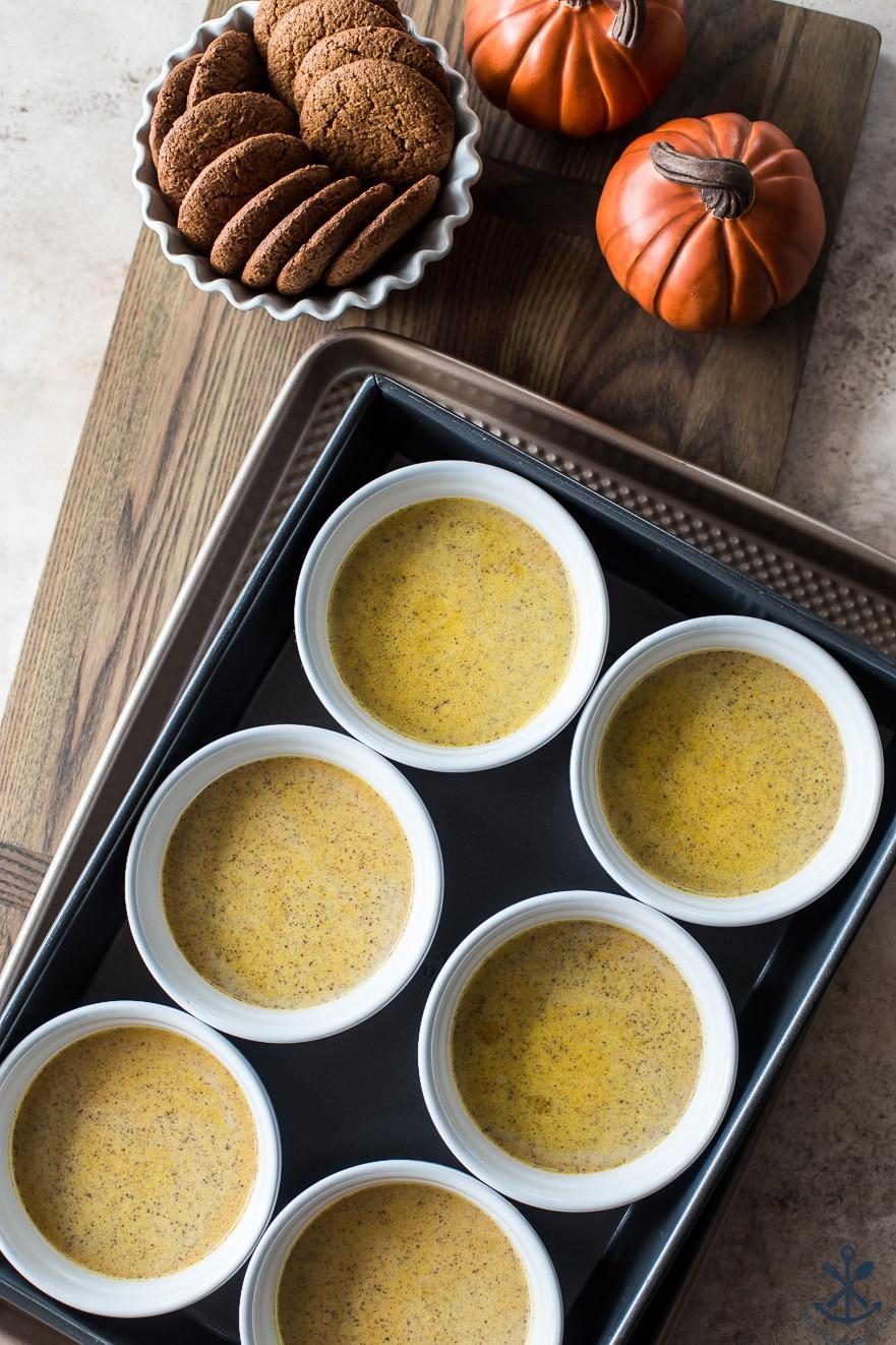 Pre-baked Pumpkin Custards with Gingersnap Crumble in white ramekins