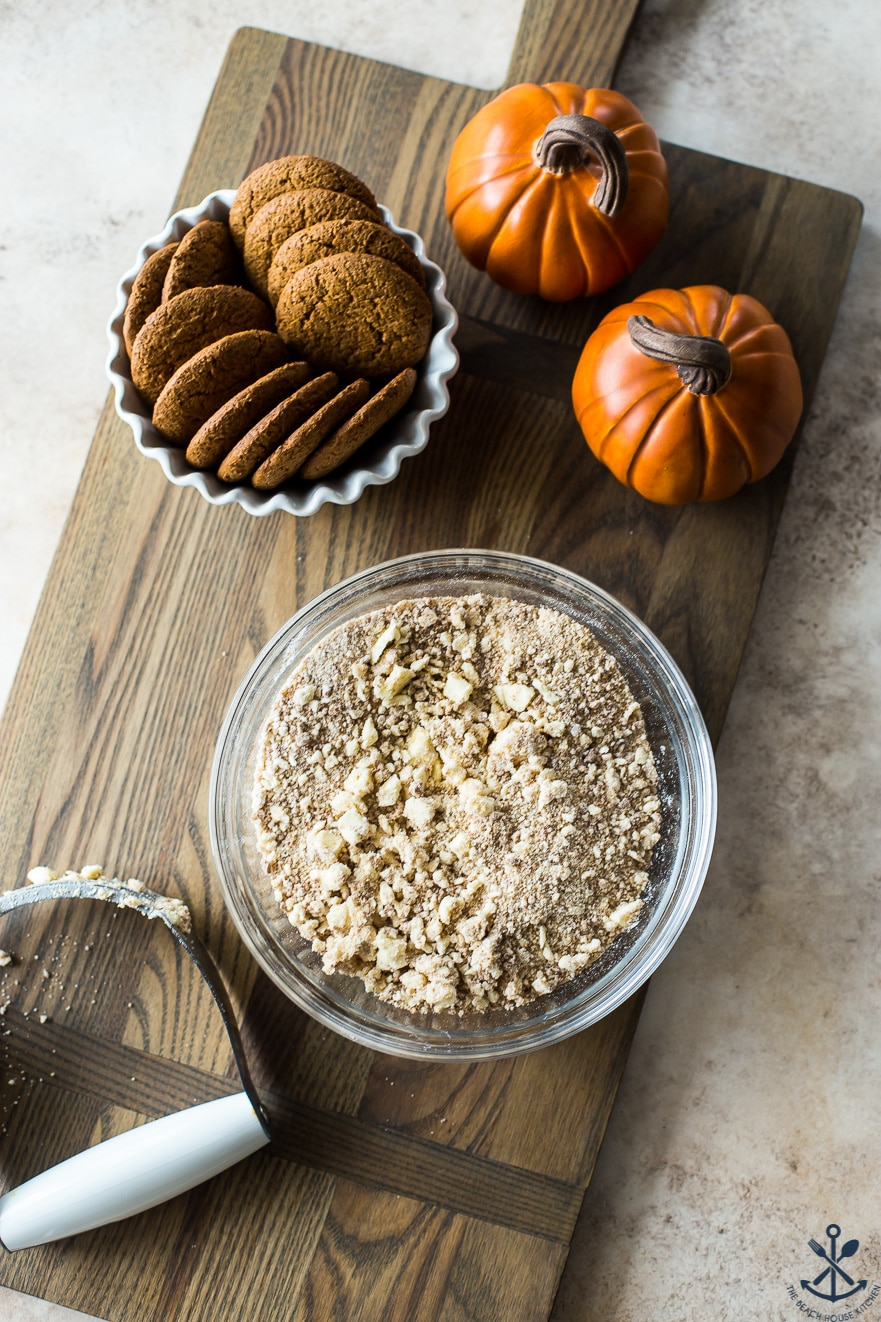 Gingersnap crumble for Pumpkin Custards with Gingersnap Crumble in a bowl with a pastry blender on a wood board