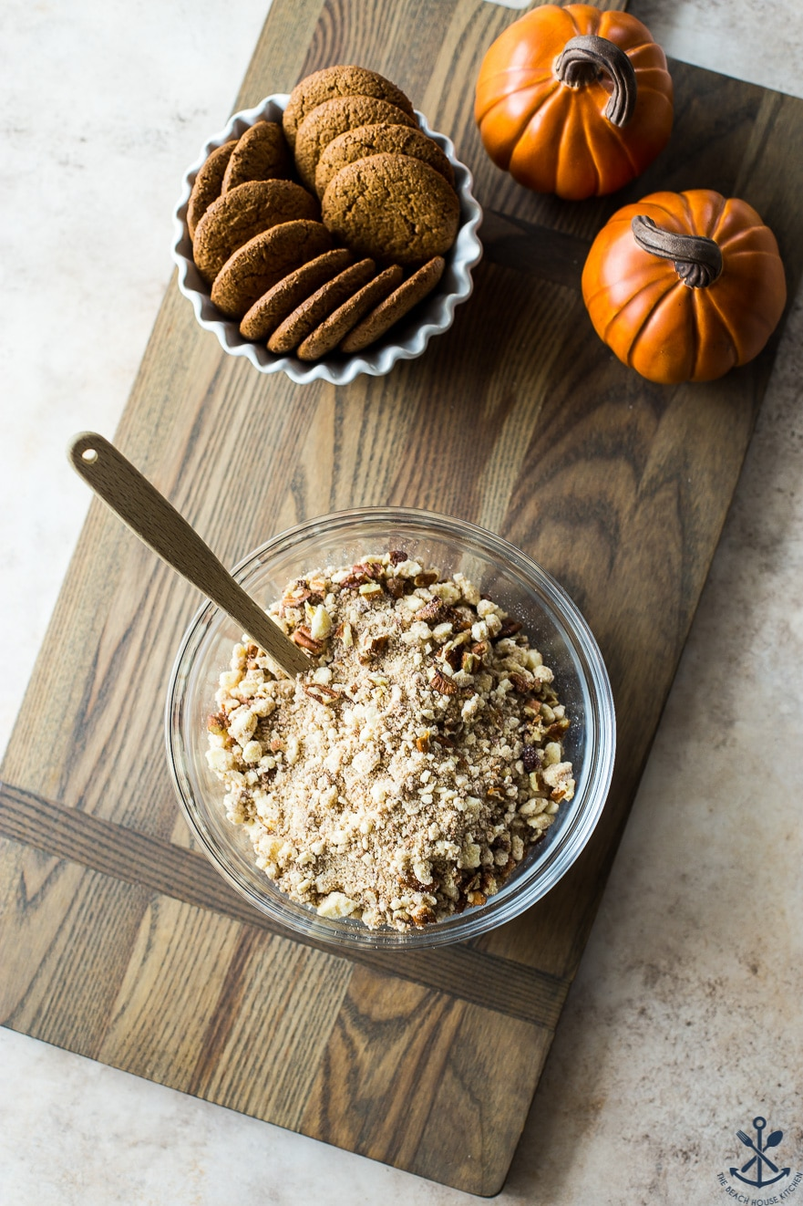 Gingersnap crumble for Pumpkin Custards with Gingersnap Crumble in a bowl on a wooden board