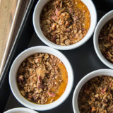 Pumpkin Custards with Gingersnap Crumble in white ramekins in a roasting pan