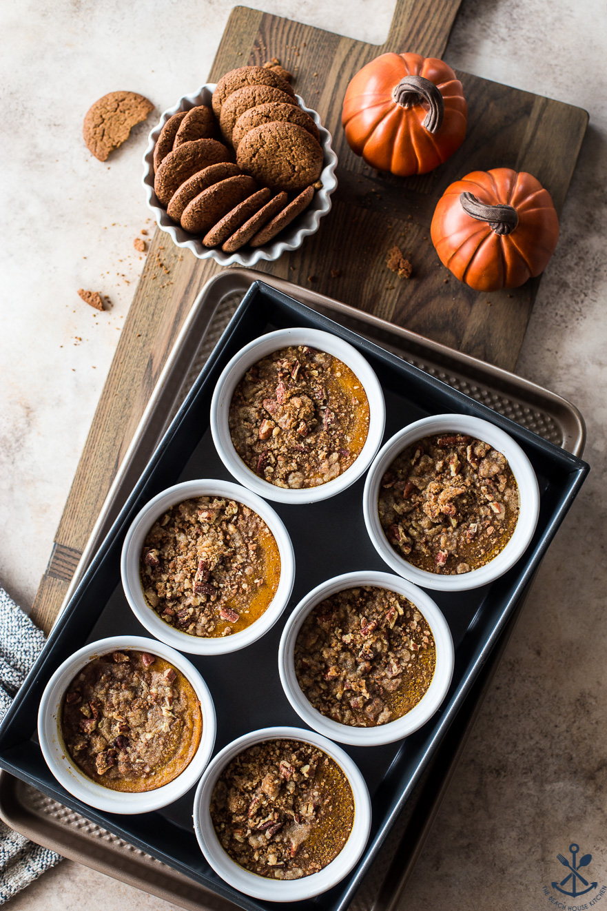 Pumpkin Custards with Gingersnap Crumbles in white ramekins on a wooden board