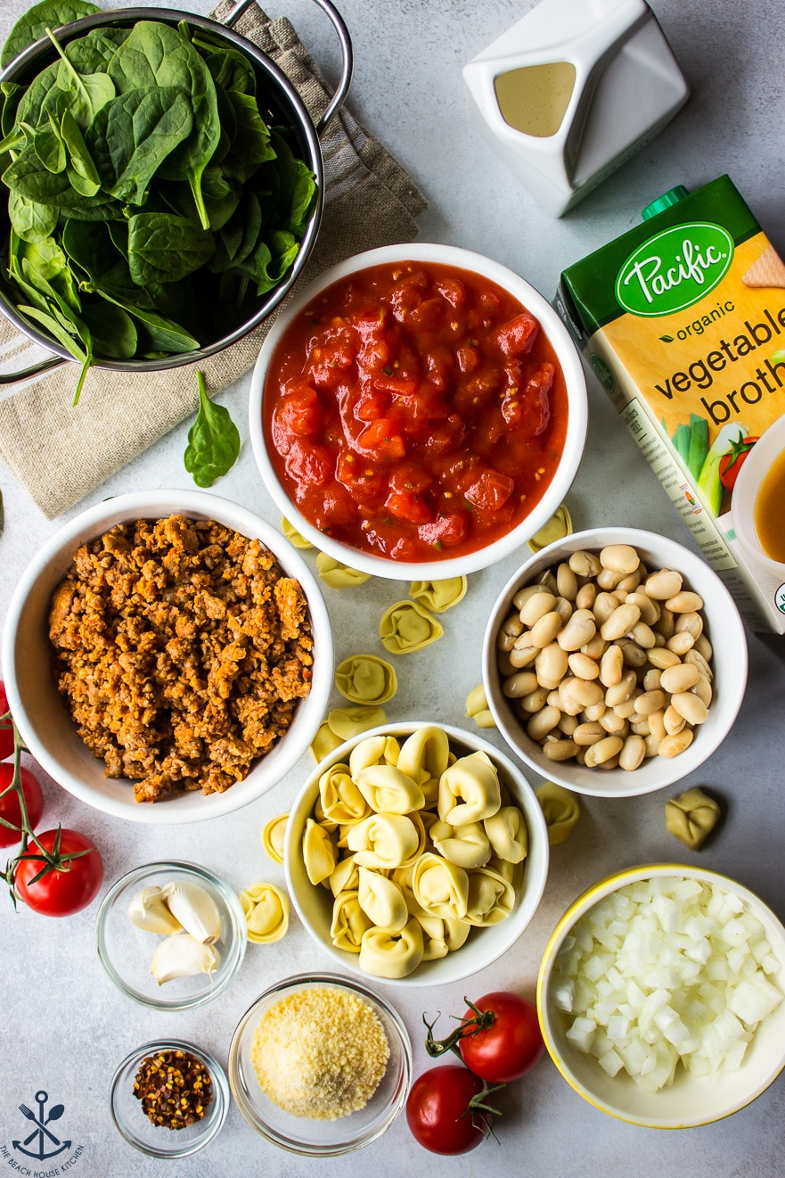 Overhead photo of ingredients for tomato tortellini stew in white bowls