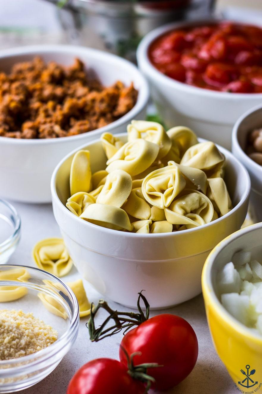 Ingredients for tomato tortellini stew in white bowls
