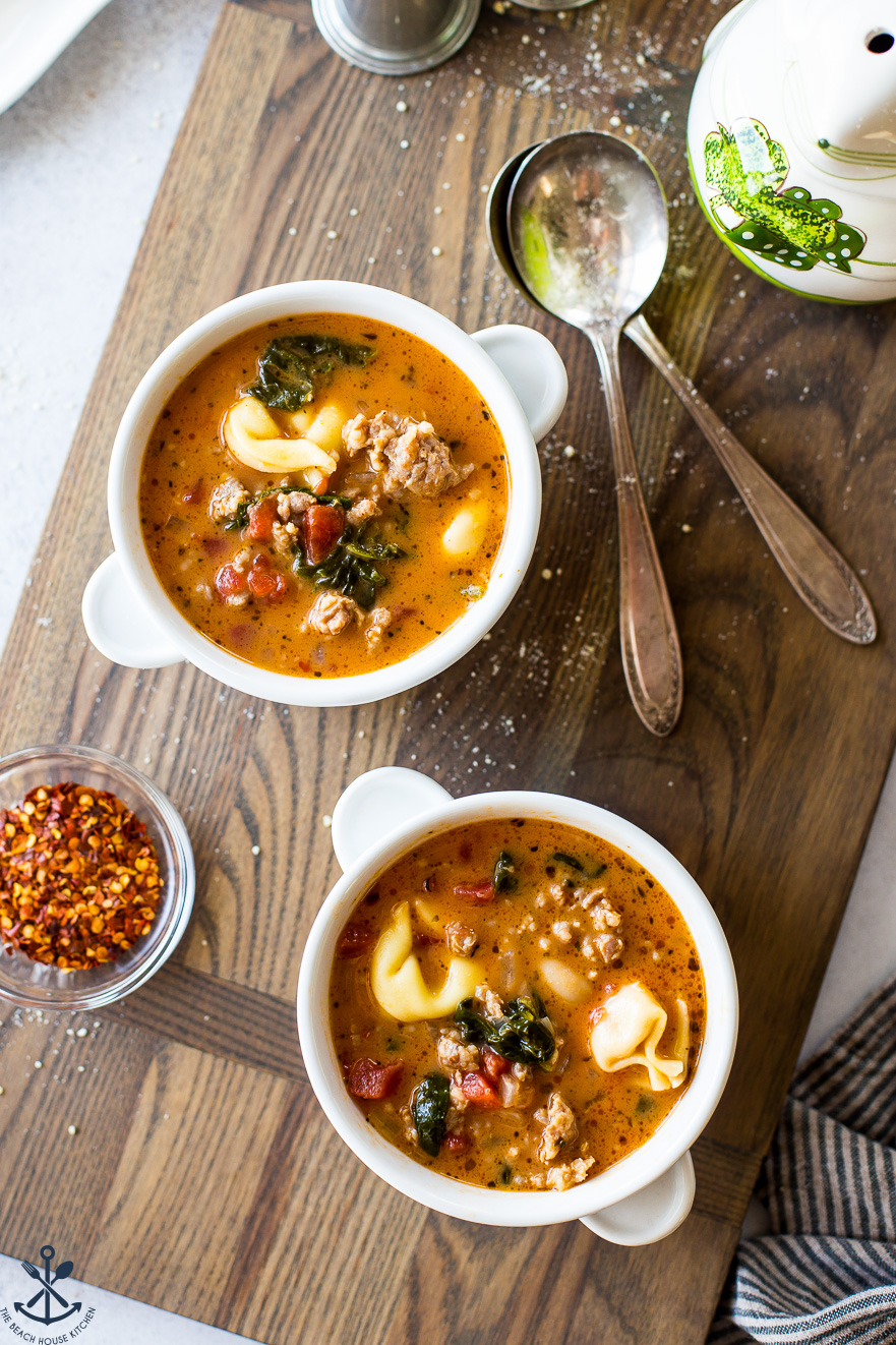 Overhead photo of two white bowls on a wooden board filled with tomato tortellini stew