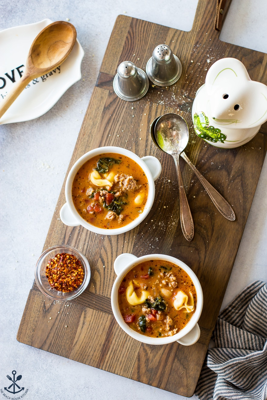 Overhead photo of white bowls on a wooden board filled with stew