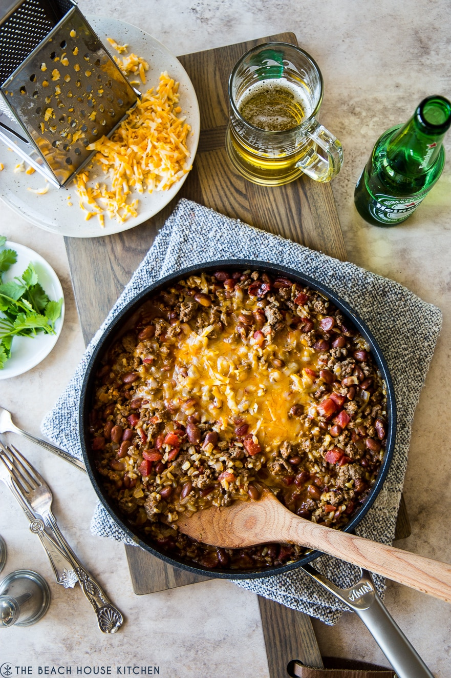 Overhead photo of beef burrito skillet on a wooden board with a plate of shredded cheddar cheese