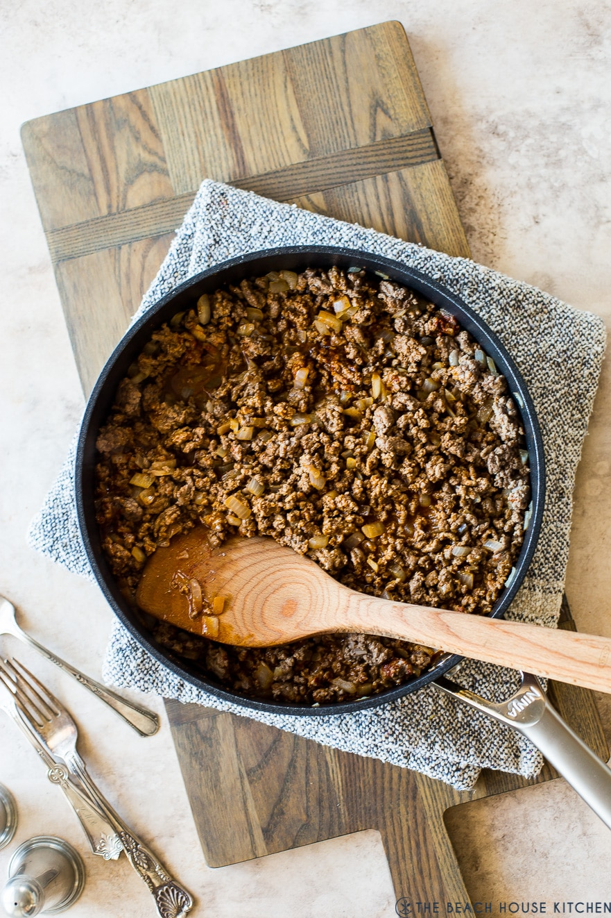 Overhead photo of cooked taco meat in a skillet on a wooden board with a wooden spoon on top of the meat