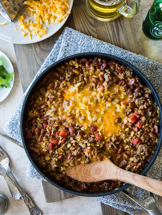 Overhead photo of beef burrito skillet on a wooden board with a plate of shredded cheese