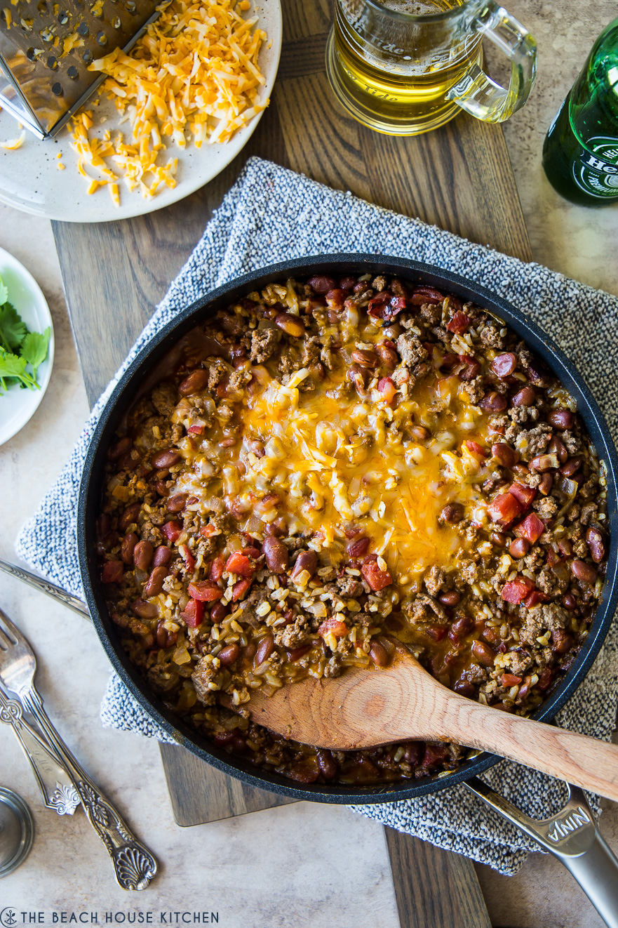 Overhead shot of the delicious Beef Burrito Skillet made in a skillet with a wooden spoon on top of it