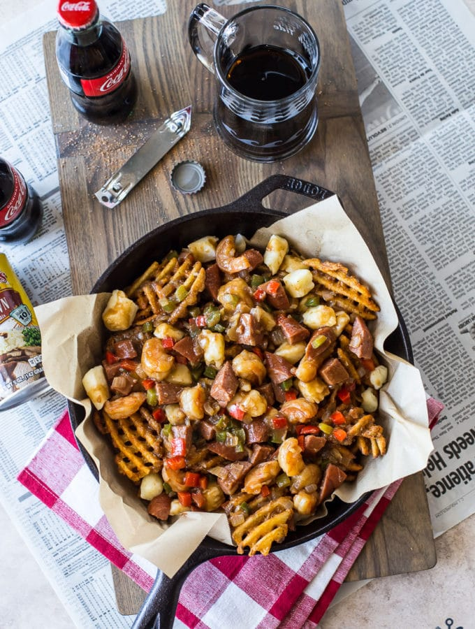Overhead photo of Cajun poutine in a skiller on a wooden board