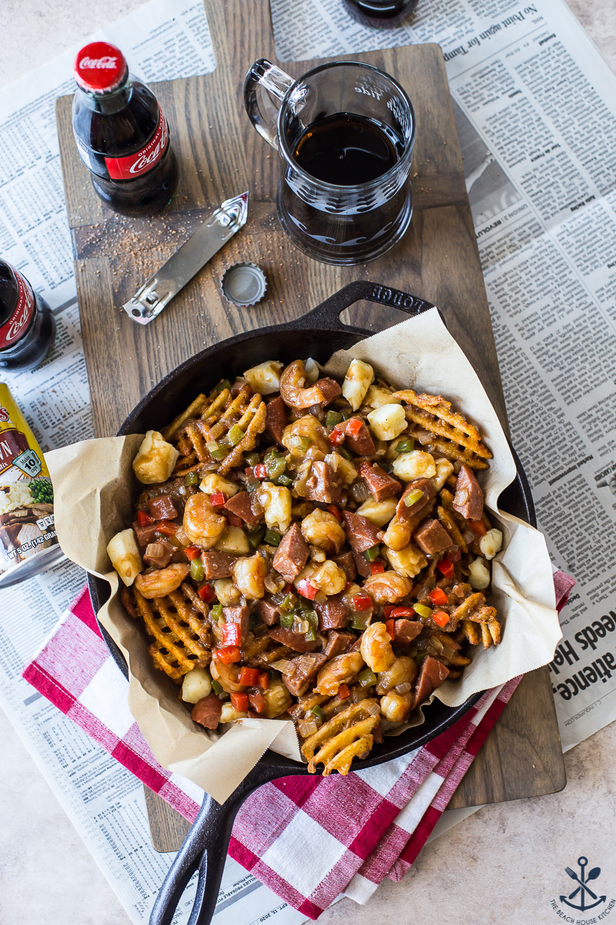 Overhead photo of Cajun poutine in a skillet on a wooden board