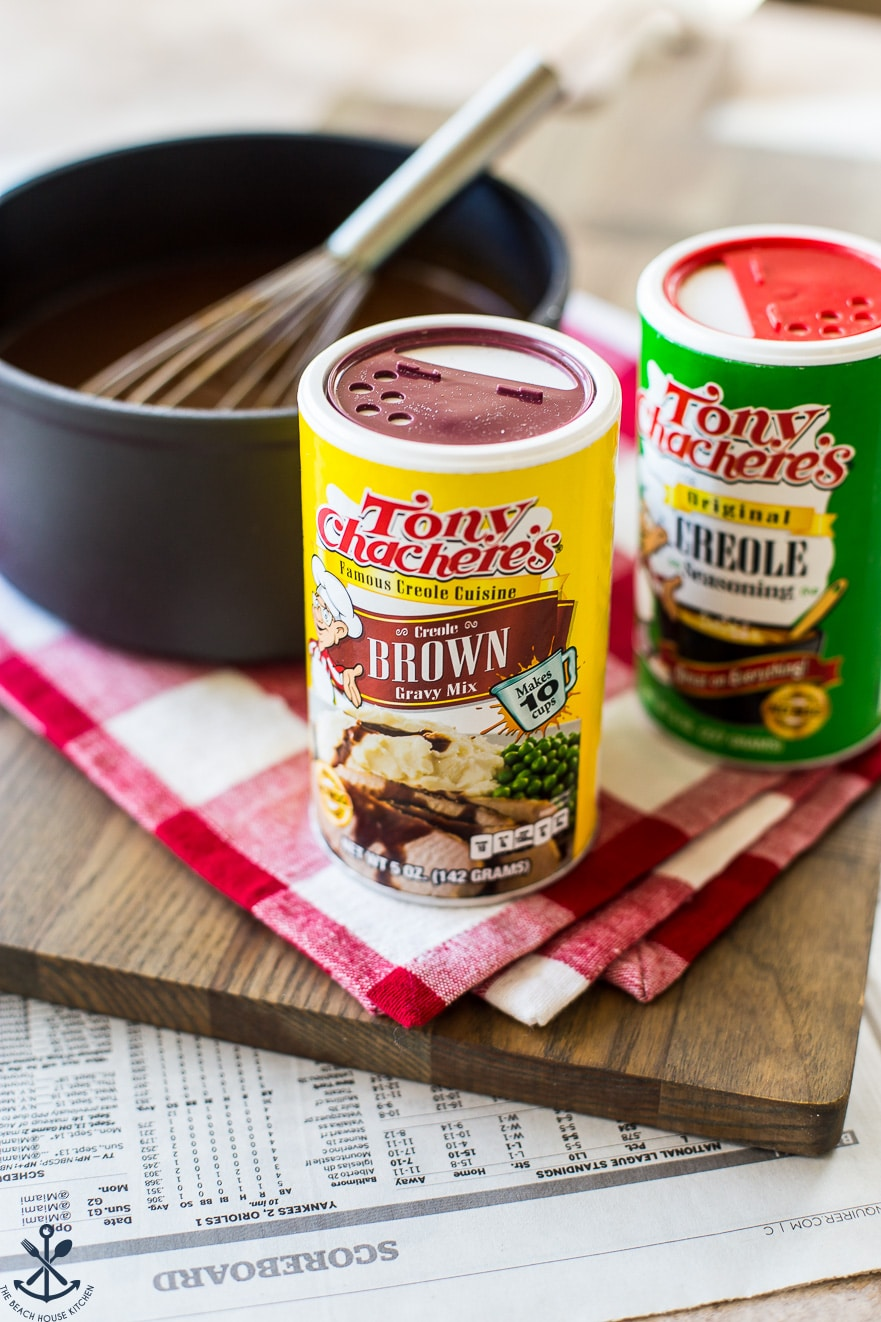 Tony Chachere's brown gravy mix and creole seasoning cans on a wooden board