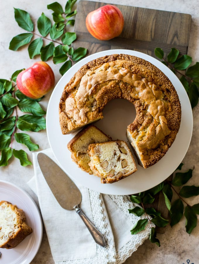 Overhead photo of Jewish Apple Cake on a white cake plate surrounded by apples and greens